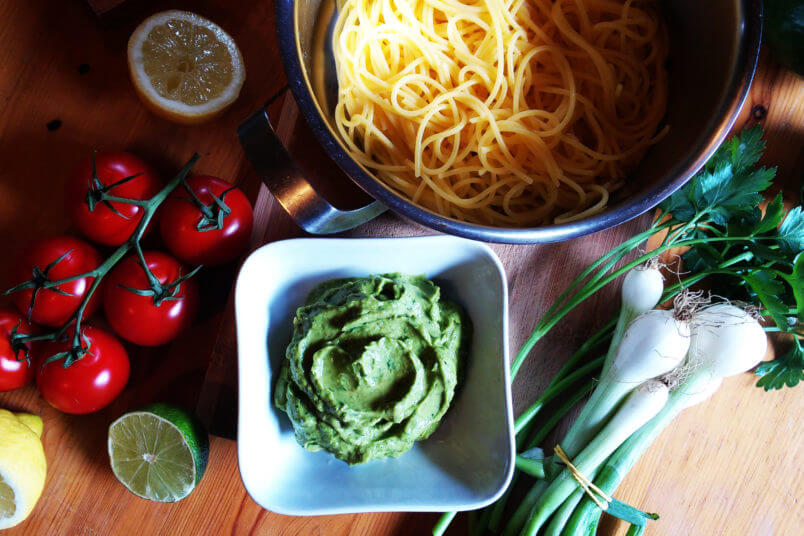 Pasta with creamy avocado sauce, herbs and vegan parmesan cheese