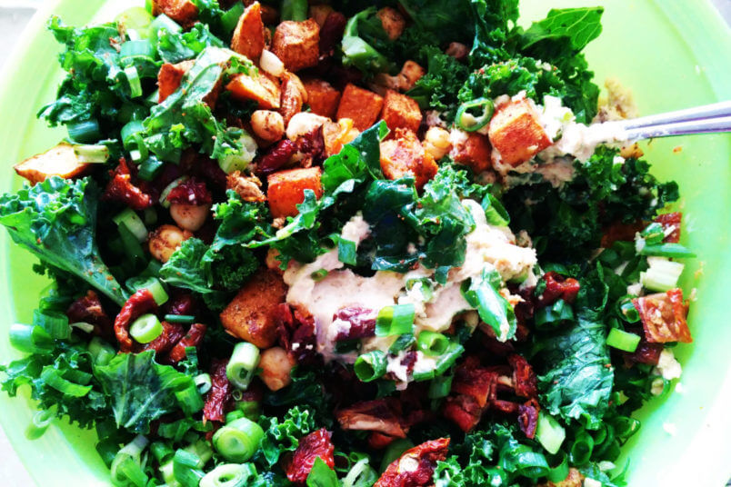 Salad with roasted sweet potatoes, chickpeas, dried tomatoes, hummus and kale